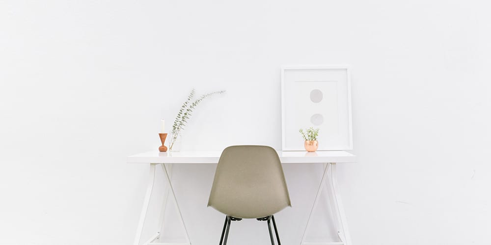 organized desk with chair against white wall