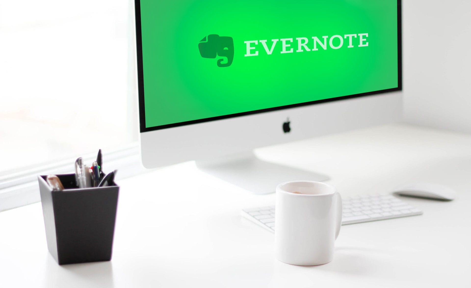 White desk with coffee mug, pencil holder, and iMac screen with Evernote logo on screen